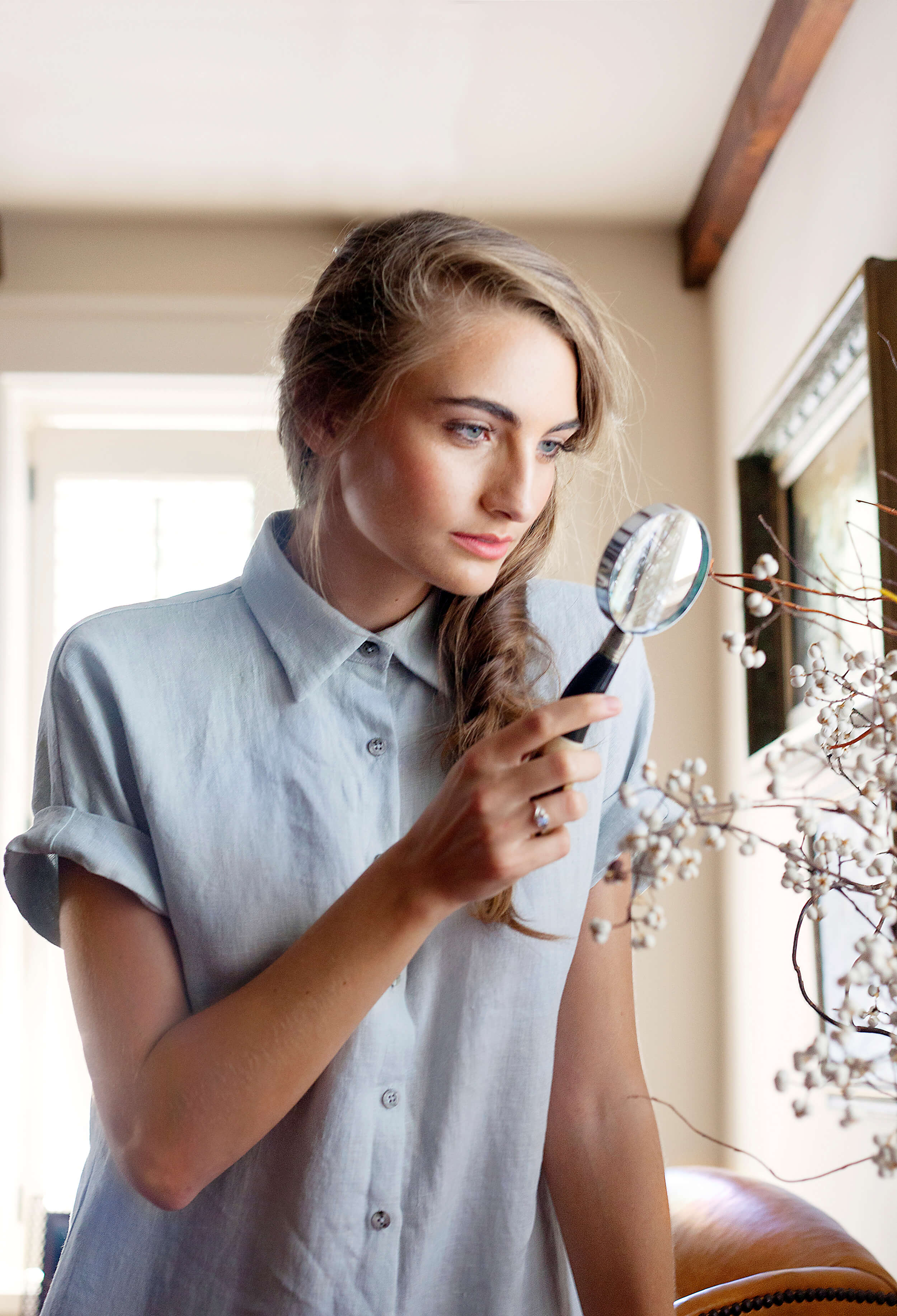Photograph of a model looking through a magnifying glass by Margaret Wright Photoraphy